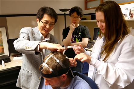 Tai Sing Lee helps student Elizabeth Ottens attach an EEG sensor to CMU postdoctoral student Jason Samonds during an experiment at the Center for the Neural Basis of Cognition at the Mellon Institute in Oakland. Carnegie Mellon student Lingzhang Jiang observes.