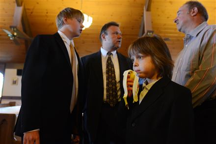 Andrew Warhola, 8, grabs a snack after his first communion, while his cousin Matthew talks with Andrew's uncles, Mark Warhola, center, and Jeffrey Warhola, right.