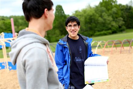 Suvir Mirchandani, who got national publicity for research he did on how the government could save millions of dollars in printing costs, talks to a classmate while doing an outdoor physics experiment.