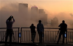In this October 2019 file photo, fog circles around the skyline as photographers take in the view before sunrise from an overlook on Grandview Avenue in the Mount Washington neighborhood of Pittsburgh.