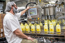 JT Bendel, machine operator at Turner Dairy Farms, works a machine as half gallon lemonades on a conveyor belt make their way to be packaged, Thursday, March 5, 2020, at Turner Dairy Farms in Penn Hills.