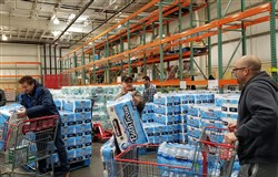 Customers quickly grab toilet paper after it was restocked at the Costco in Robinson March 15. The store told customers that only one package of toilet paper and one of paper towels would be sold to each customer.