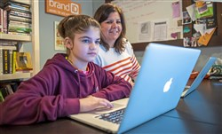 Alexa Kartofilis, 12, looks at puppies for sale on her computer as her mother Rachel Gogos works from home.