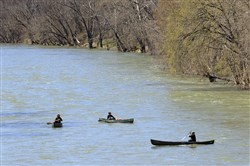 A group of kayakers practice social distancing while floating down the Greenbrier River in Ronceverte, W.Va., on March 26, 2020.