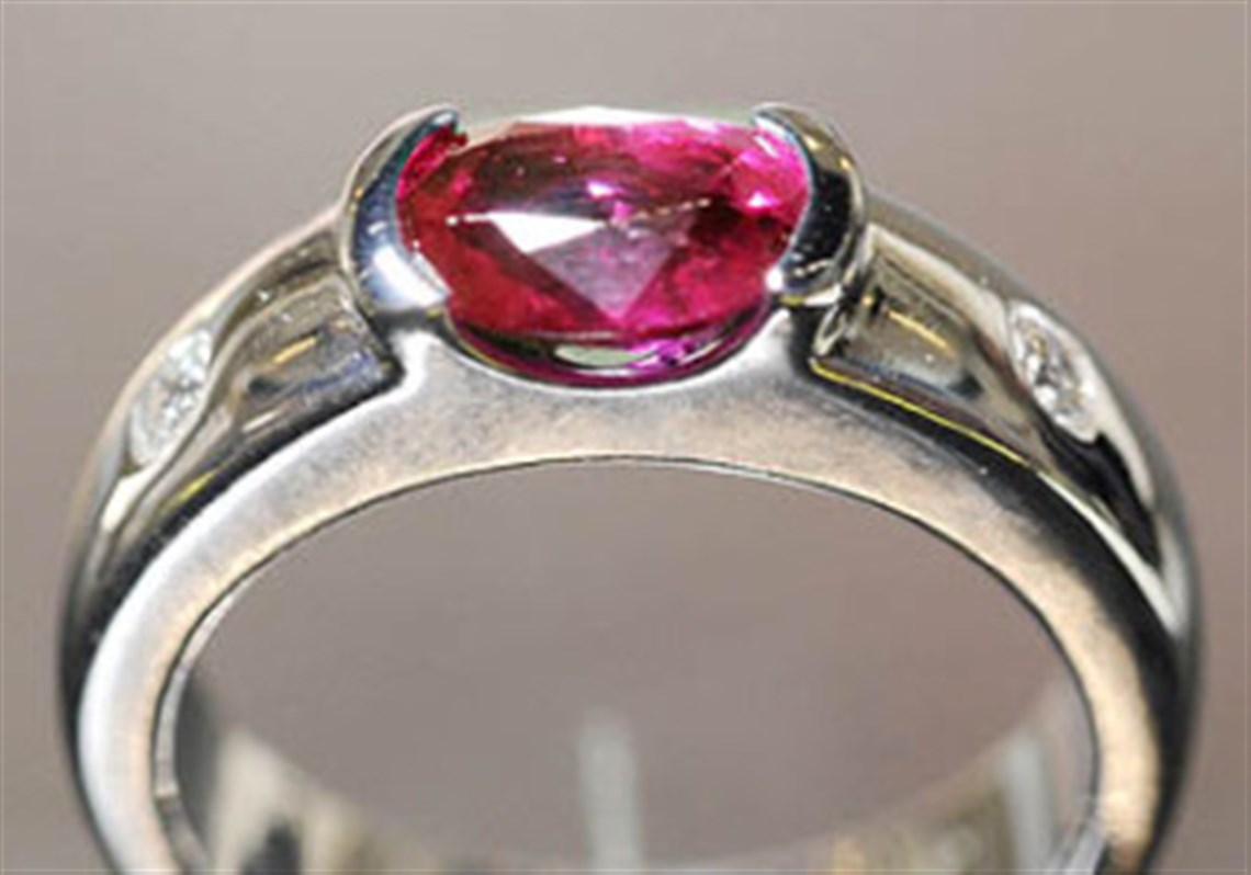 A White Gold Fashion Ring Containing A Fine Oval Ruby Specially Channelset  And Two