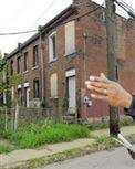 Jerome Jackson of Homewood's Operation Better Block at blighted row houses owned by a California company, RFS Investment LLC.
