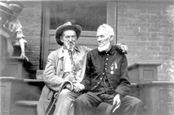 An unidentified Confederate and Union soldier share memories at the 50th anniversary reunion at Gettysburg, Pa., in 1913.