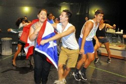 "Carlos Jimenez as Graffiti Pete wraps Amanda Serrano, portraying Daniela, in a Puerto Rican flag as they rehearse a scene for ""In the Heights."""