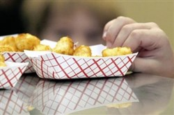 Little fingers reach for tater tots during lunch at an elementary School in Brandon, Miss.