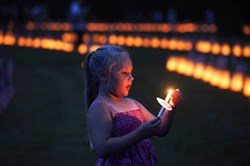Taylor Lawrence, 5, of Mechanicsburg, Cumberland County, holds a candle during a vigil Sunday at Soldiers' National Cemetery at Gettysburg. Luminaria mark each of the more than 3,500 graves of soldiers killed in 1863 in the Battle of Gettysburg.