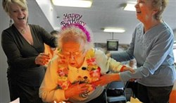 Icie Clark blows out the candles on her 105th birthday cake while celebrating with her daughter, Jean McDonough of Forest Hills, right, and Anna Mason, the property manager at Swissvale Towers, during a birthday party in 2012.