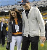 Chicago Bears fan Ashton Kutcher, right, and Mila Kunis walk along the sideline before a Steelers-Bears game at Heinz Field.