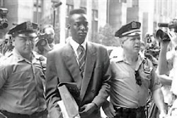 "Defendant Yusef Salaam walks into courthouse flanked by police officers in ""The Central Park Five."""