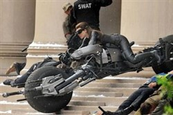 "Catwoman, played by Anne Hathaway, barrels out of the Mellon Institute during filming of ""The Dark Knight Rises."""
