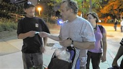 Operation Safety Net founder, Dr. Jim Withers, hands medicine to a homeless man while making the rounds in Downtown Pittsburgh in 2011.