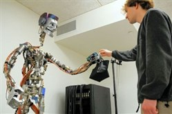 Disney Research associate Matthew Glisson hands a bag to a robot during a simulated demonstration at the Disney Research lab on the Carnegie Mellon University campus in Oakland. Researchers have developed a robot that is capable of analyzing human motions in order to give and receive items.
