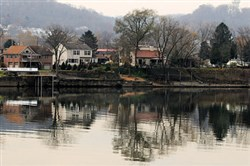Part of Neville Island reflects in the calm waters of the Ohio River, in this view from Glenfield.