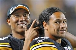 In this September 2010 photo, Hines Ward jokingly makes cutting motions around Troy Polamalu's hair. A few days prior Head & Shoulders, for which Polamalu is a spokesman, had insured his hair for $1 million.