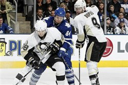 Maple Leafs forward Mikhail Grabovski battles for the puck with Penguins defenseman Kris Letang and forward Pascal Dupuis during a game at the Air Canada Centre in Toronto.