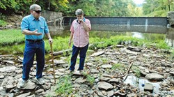 Verna Presley covers her nose to block out the smell of rotting fish as she walks along Dunkard Creek in 2009 with her husband, Ed, on their property near the village of Brave in Greene County.