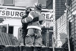 Two firefighters embrace outside a Bricelyn Street home in Homewood where three Pittsburgh firefighters died battling a blaze on Valentine's Day 1995.
