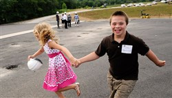 Aleah Walendziewicz, 10, of Oakmont runs around the rubberized baseball field with her brother Josh, 11, after the naming ceremony at Bill Mazeroski Miracle Field in Murrysville.