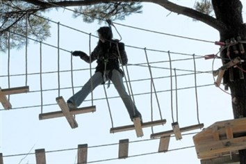In the trees An employee of Go Ape works her way through the new treetop obstacle course -- a series of zip lines, rope ladders and swings -- during training for workers at the recreational course set to open this spring in North Park.
