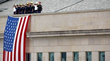 9/11 at the Pentagon Emergency response workers stand above a U.S. flag at the spot where American Airlines Flight 77 slammed into the building, killing 184 people. President Bush dedicated a memorial during the service there yesterday.