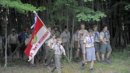 A banner tale Drake Palmer, 12, of Troop 301 in Robinson, carries the flag to the flag-lowering ceremony at Camp Liberty.