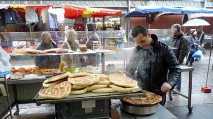 A cafe near the Marche de Saint-Denis A man grills flatbread for sandwiches sold outside Au Royaume de L''Oriental, a North African restaurant and cafe near the Marche de Saint-Denis.