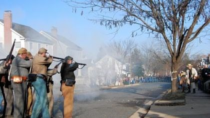 A Confederate unit A Confederate unit fires upon advancing Union soldiers on Hanover Street in Fredericksburg, Va. A photographer in period garb, right, sets up to take a picture.