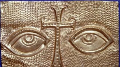 A reproduction of a gold votive plaque found wedged in St. Peter's tomb. A reproduction of a gold votive plaque found wedged in St. Peter's tomb. The image of eyes, separated by a Latin cross, and the location of the votive, may mean that a pilgrim left it in gratitude for the saint's intercession with Christ to help cure an eye problem. Archaeologists believe grave robbers missed the plaque because it was so carefully hidden.