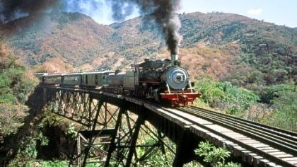 "A steam train A steam train crosses the bridge below Agua Caliente, Guatemala. This steel structure was subsequently dismantled by scrap metal thieves after the declaration of ""lesivo."""