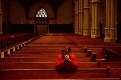 A woman kneels to pray A woman kneels to pray Wednesday for Pope Francis at St. Paul Cathedral in Oakland.