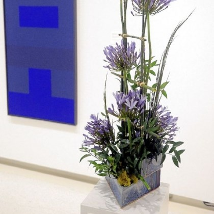 "'Abstract Painting Blue' Arrangement by Marie Mueller and Mary Finley is paired to the painting ""Abstract Painting Blue"" by Ad Reinhardt."