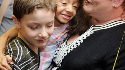 Adoption day Lexie Jae Bouchard, 9, gets a hug from her brother Alex, 11, and her mom, Carol, after officially being adopted in a hearing yesterday in Allegheny County Family Court on National Adoption Day.