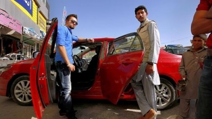 "afghan cars Architect Mohammad Azizi, left, bought a used Toyota Corolla that came from Canada five months ago in Kabul, Afghanistan. Cars from the U.S., Canada and Europe are at a premium in Afghanistan, even ones termed a ""total loss"" by U.S. insurance companies are desired."