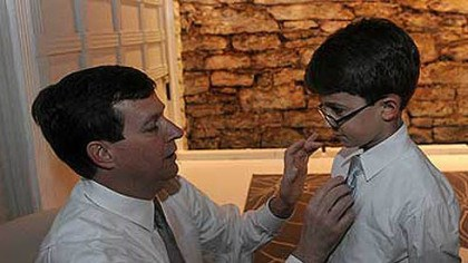 Alexander Neil Alexander adjusts his son Patrick's tie before the beginning of a 20th anniversary party Neil and his wife Suzanne held on March 24. Muscles in Neil's hands have started to atrophy due to the progression of ALS, which he was diagnosed with in 2011.