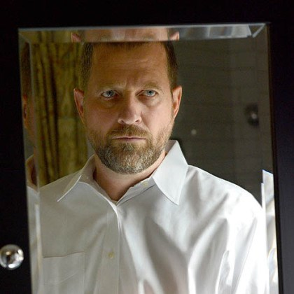 ALS_research_001 Neil Alexander looks into the bathroom mirror at his home in O'Hara on Thursday. Because of the deterioration of his hands from amyotrophic lateral sclerosis he has grown a beard and keeps his hair very short.