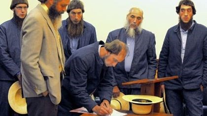 Amish In a file photo, Johnny Mullet signs documents during a preliminary hearing in October in the Holmes County Courthouse in Millersburg, Ohio. In the foreground is his attorney, Andy Hyde, and behind him, from left to right, are Lester Mullet, Daniel Mullet, Levi Miller and Eli Miller.