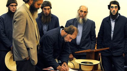 Amish in court Johnny Mullet signs documents during a court appearance in the Holmes County Courthouse in Millersburg, Ohio. In the foreground is his attorney, Andy Hyde, and behind him, from left to right, are Lester Mullet, Daniel Mullet, Levi Miller and Eli Miller.