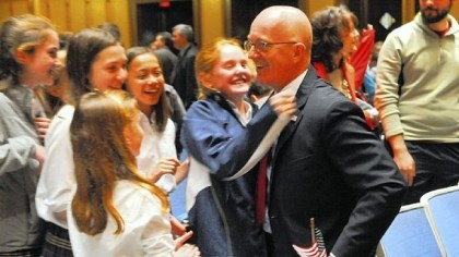 Aquinas Academy Students from Aquinas Academy give congratulatory hugs to teacher and director of admissions Juan Mata after his naturalization ceremony Friday at Soldiers & Sailors Memorial Hall & Museum in Oakland.