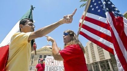 Arizonians argue Andy Hernandez, left, carrying a Mexican flag, and Allison Culver, carrying an American flag, argue Monday over Arizona's immigration law outside the State Capitol in Phoenix.
