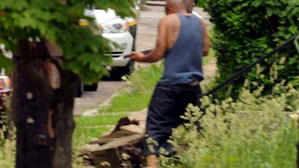 Armed man A man emerges from a house in Larimer, armed with a shotgun. He was shot by police after they ordered him to drop his weapon.