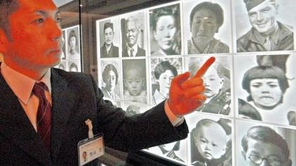 Army Air Force Cpl. John Long Jr. Curator Shigeru Aratani, of the Hiroshima National Peace Memorial Hall for the Atomic Bomb Victims, points at a photo of Army Air Force Cpl. John Long Jr., top right, grinning under his khaki side cap, among other victims at the memorial in Hiroshima.