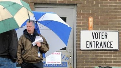 At the polls Ron Pasic has won the nomination to the West Allegheny school board on both tickets in unofficial results. Here, he waits to greet voters outside the North Fayette municipal building.