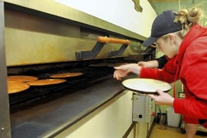 augustines2 Alex Hill loads pizza crusts into the ovens at Augustine's pizza in New Castle, which makes between 2,400 and 3,000 crusts per day. The pizza is now sold at PNC Park, Giant Eagle and other venues.