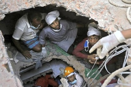 Bangladeshi rescue workers Bangladeshi rescue workers search for survivors as they are seen Sunday through a hole in the roof a building that collapsed Wednesday in Savar, near Dhaka, Bangladesh.