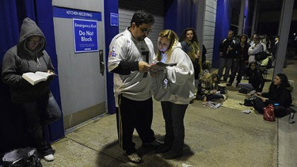 bargain hunters Jeremy Martin and his wife Jennifer Martin of Baltimore, Md., look through ads as they wait in line outside Toys R Us in Robinson.