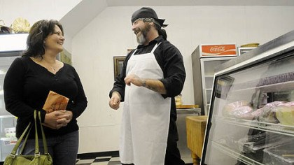Bloomfield D.J. Smulick, right, talks with customer Dawn Glasner of the South Side at his new business, D.J. Specialty Sausage and Meats, on Liberty Avenue in Bloomfield, one of several new business in the neighborhood.
